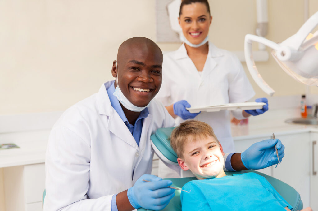 dentist with young patient and female dental assistant smiling
