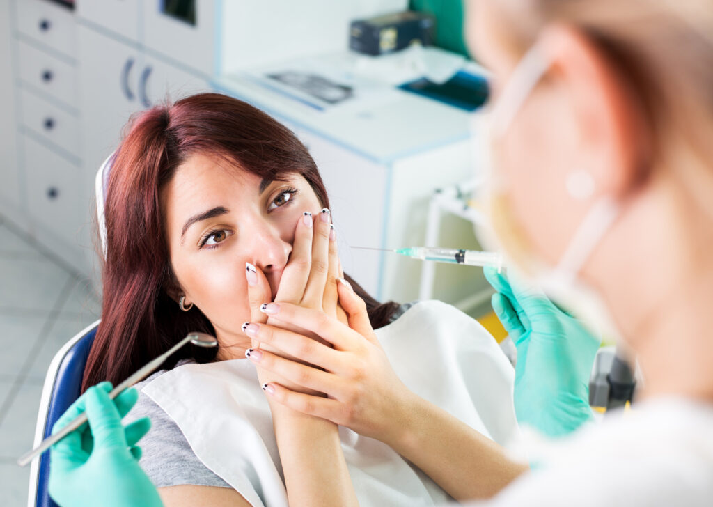 Young female dentist giving anesthesia to the patient before dental surgery. The patient in fear holds hands over mouth.
